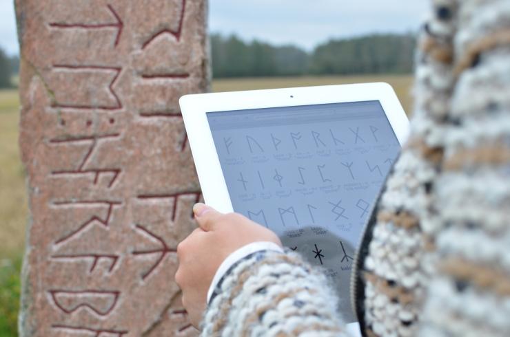 Jenny tyder runskrift på runstenen i Järsberg