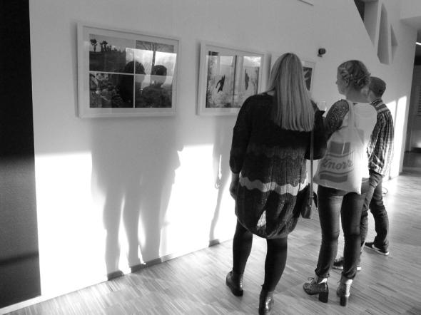 Besökare på utställningen kollar fotografierna